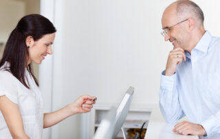 man paying receptionist at dentists office