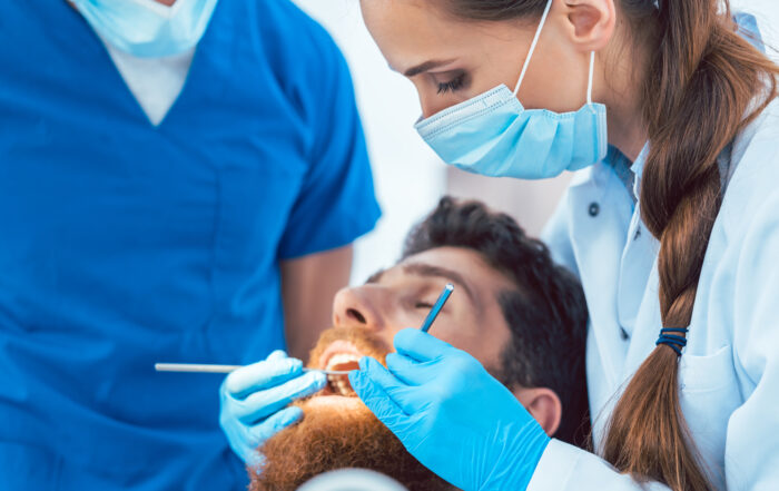 hygienist performing dental cleaning on male patient